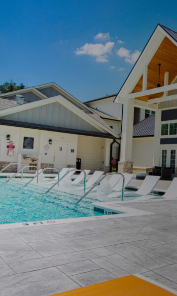 pool view with in-water chairs and partial view of clubhouse