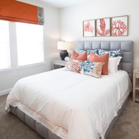 bedroom with wall art, bed, decorative pillows, and lamps